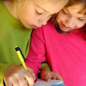 2 girls working together in a workbook